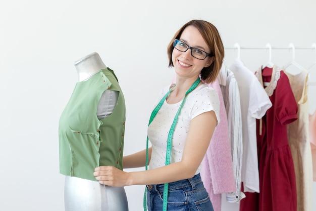 Positivo carino sorridente giovane sarta donna in bicchieri con un metro a nastro facendo un nuovo indumento con l'aiuto di un manichino da sarto in piedi su uno sfondo bianco con prodotti di design già pronti.