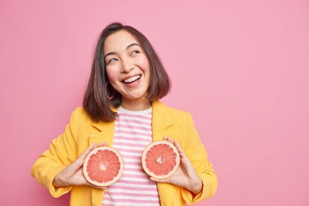 La giovane donna dai capelli scuri positiva tiene le metà del pompelmo usa gli agrumi per la cura della pelle distoglie lo sguardo felicemente vestita con abiti alla moda pose contro il muro rosa con spazio vuoto per copia