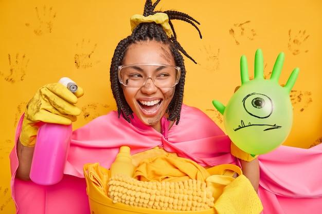 Il supereroe femminile dalla pelle scura positivo indossa occhiali trasparenti e sorrisi del mantello tiene ampiamente il detersivo per la pulizia pulisce tutto sulla sua strada posa contro il muro giallo