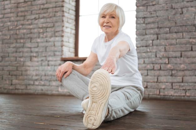 Positiva donna felice che indossa la maglietta bianca e pantaloni grigi guardando la telecamera mentre si estende il suo corpo