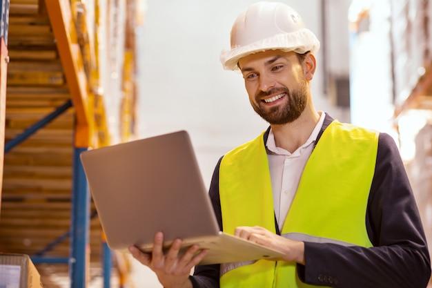Responsabile delle consegne positivo utilizzando un laptop mentre controlla il processo di lavoro
