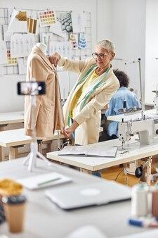 La sarta positiva presenta la nuova giacca beige mentre gira un video mentre la sarta afroamericana si siede