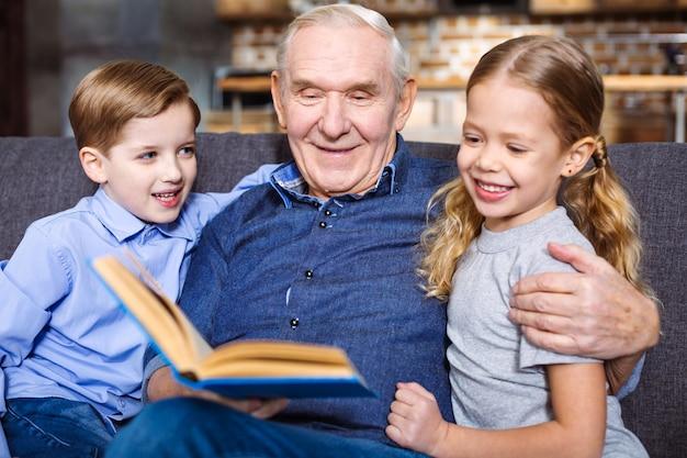 Uomo anziano positivo che legge un libro per i suoi nipoti mentre riposa a casa