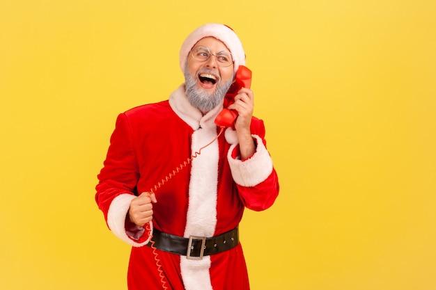 Un uomo anziano positivo con la barba grigia che indossa il costume di babbo natale che parla al telefono fisso saluta gli amici con natale e capodanno, sembra felice. colpo dello studio dell'interno isolato su priorità bassa gialla.