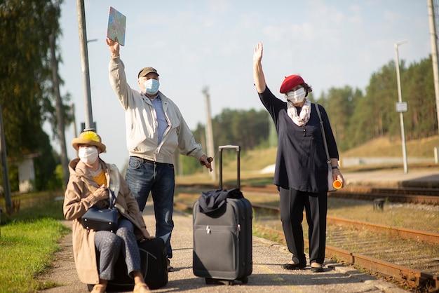 Anziani anziani positivi persone con maschere facciali in attesa del treno prima del viaggio