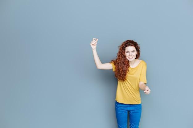 Emozioni positive. felice bella donna attraente che sorride e ti guarda mentre si tiene la mano
