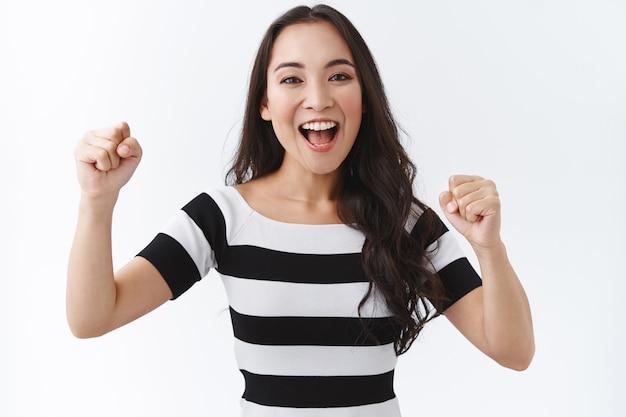 Positiva, entusiasta, bella ragazza asiatica che fa il tifo per la squadra, stringe la pompa a pugno e sorride, incoraggia qualcuno a fare del suo meglio, sorride e sostiene in piedi allegra, trionfa su sfondo bianco