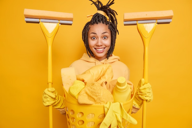 La donna etnica positiva tiene in mano due stracci che vanno a lavare