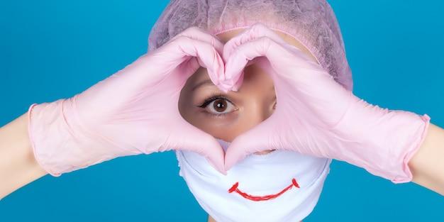 La faccia positiva di un medico mani in guanti di nitrile rosa che tengono la forma di un cuore accanto all'occhio