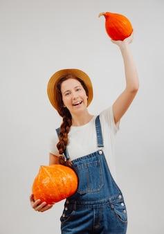 La donna positiva dell'agricoltore tiene un raccolto autunnale di zucche arancioni mature concetto di cibo biologico