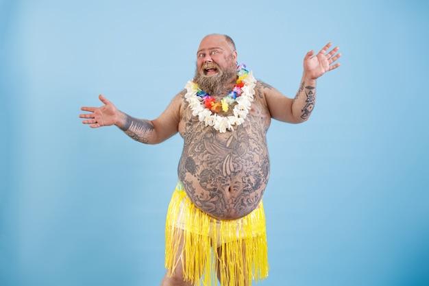 Uomo grasso positivo con tatuaggi in gonna di erba decorativa balla su sfondo azzurro