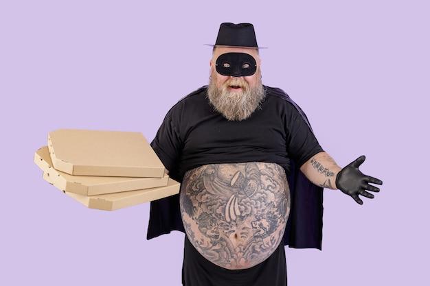 L'uomo grasso positivo in costume da zorro tiene scatole di cartone di pizza su sfondo viola