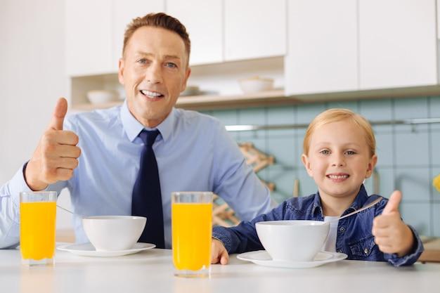 Padre e figlia positivi che si siedono al racconto e che mostrano i pollici aumentano i gesti