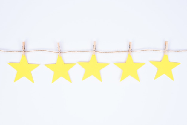 Concetto di feedback positivo. primo piano foto di cinque piccole stelle dorate appese al filo attaccato con piccole mollette isolato sfondo bianco