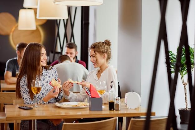 Amici femminili positivi che chiacchierano e che mangiano in pizzeria.