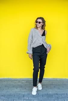Modello femminile positivo che posa in maglione lavorato a maglia grigio in occhiali da sole vicino alla parete gialla, all'aperto