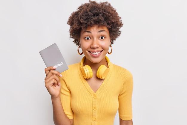 La turista femminile positiva che andrà in vacanza tiene il passaporto che conferma la sua identità indossa le cuffie stereo intorno al collo vestita con un maglione casual giallo