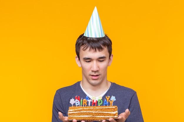 Positivo giovane ragazzo asiatico divertente con un berretto e una candela accesa e una torta in mano in posa su una superficie gialla