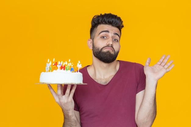 Giovane ragazzo positivo e divertente con un berretto e una candela accesa e una torta fatta in casa nelle sue mani in posa sopra