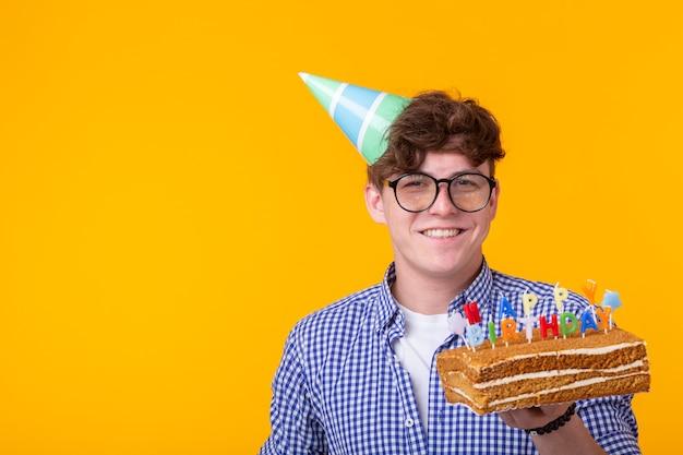 Positivo giovane ragazzo divertente con un berretto e una torta fatta in casa nelle sue mani in posa su una parete gialla