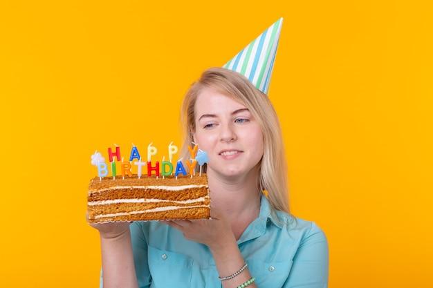 Giovane donna divertente positiva con un berretto e una torta fatta in casa nelle sue mani in posa su una superficie gialla. anniversario e concetto di compleanno.