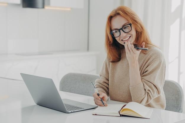La donna allo zenzero positiva in abiti casual registra un messaggio audio o uno smartphone mentre lavora al laptop