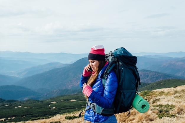 Positiva ragazza parla al telefono durante un'escursione attraverso il grand canyon utilizzando una buona comunicazione mobile, Foto Premium