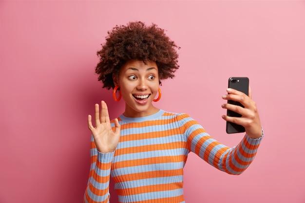 Positiva bella donna afroamericana parla selfie e onde mano alla fotocamera dello smartphone sorride felicemente indossa il ponticello a righe a maniche lunghe isolato sopra la parete rosa