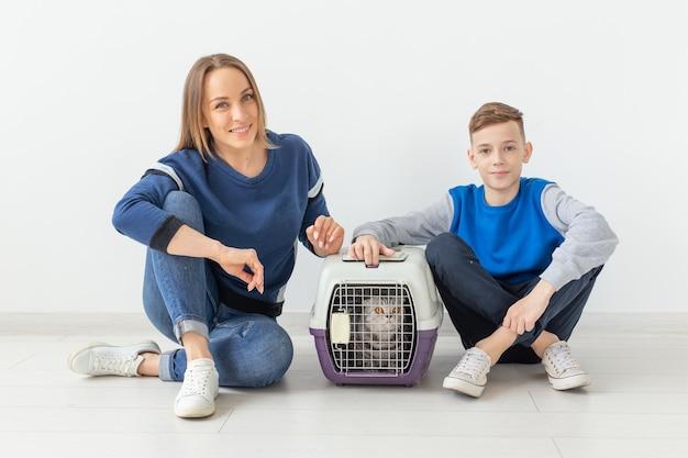 Madre e figlio di bell'aspetto positivi lanciano il loro bellissimo gatto grigio scottish fold nel loro nuovo