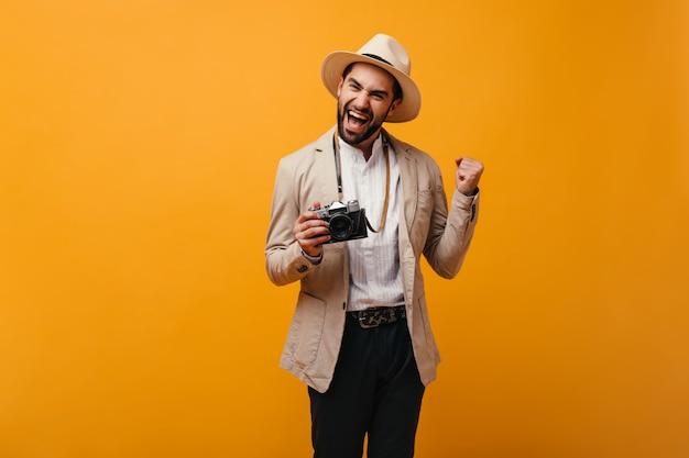Ragazzo positivo che posa felicemente sul muro arancione e tiene in mano una fotocamera retrò
