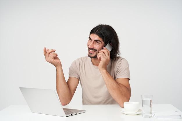 Ragazzo positivo, uomo d'affari felice con barba e capelli neri. concetto di ufficio. seduto sul posto di lavoro e parlare al telefono. guardando con il sorriso a sinistra allo spazio della copia, isolato sopra il muro bianco