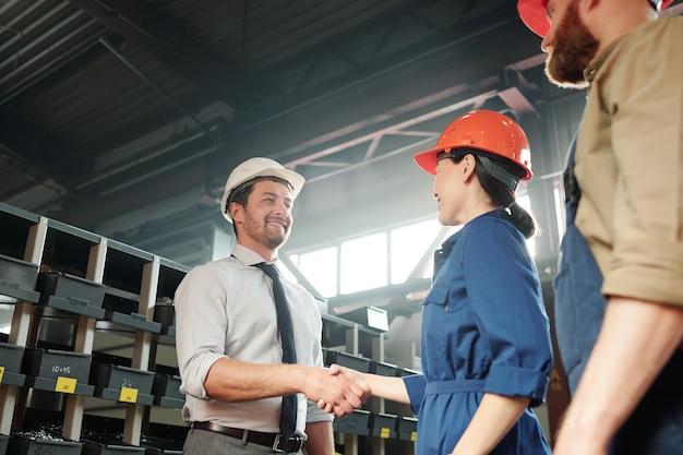 Uomo d'affari bello positivo nella stretta di mano dell'elmetto protettivo con l'ingegnere di fabbrica nel negozio contemporaneo dell'impianto industriale