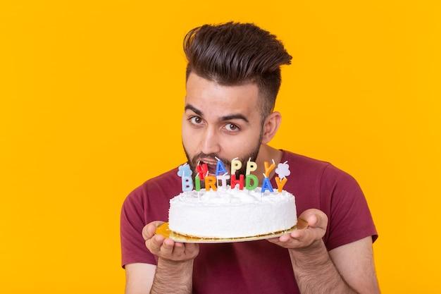 Positivo bel giovane hipster uomo in t-shirt bordeaux che tiene torta di congratulazioni con iscrizione buon compleanno in posa su uno sfondo giallo. concetto di congratulazioni e anniversari.