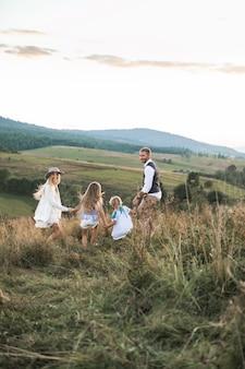 Famiglia felice positiva che funziona nel campo del paese