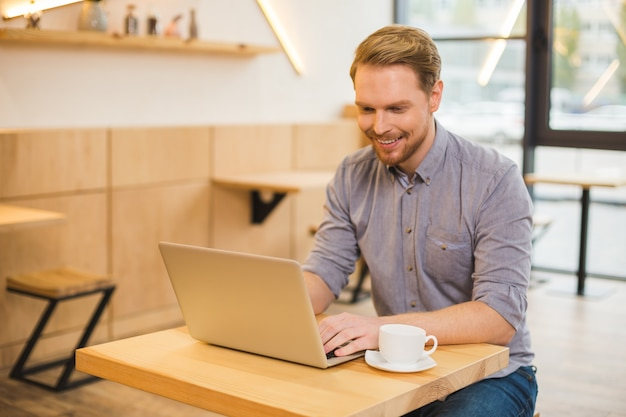Uomo gioioso felice positivo che si siede nella caffetteria e lavora al computer portatile mentre si gode il suo lavoro