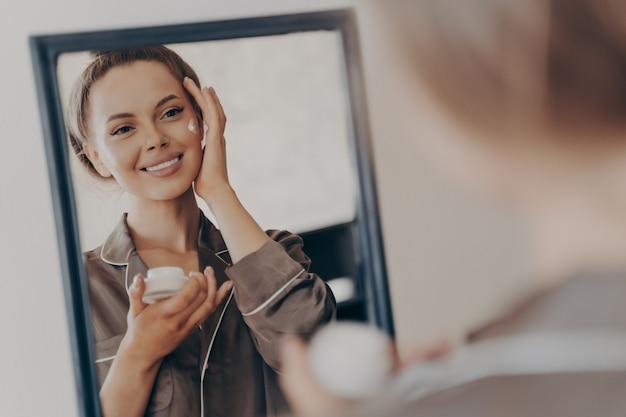 Positiva giovane donna felice in pigiama sorridente, applicando la crema per il viso e guardandosi allo specchio, signora attraente che fa routine di bellezza mattutina in camera da letto a casa. concetto di cura della pelle