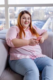 Donna gioiosa positiva di buon umore mentre è seduta sul divano con il suo smartphone