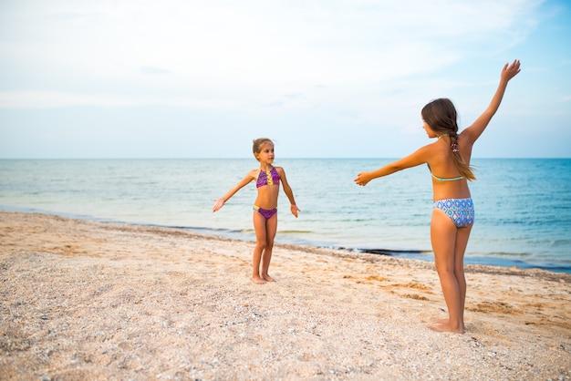 Le sorelle bambine positive giocano a giochi attivi sulla spiaggia sabbiosa durante le vacanze estive in una soleggiata giornata estiva calda