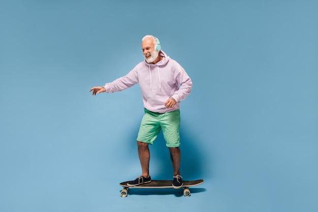 Uomo positivo in abito street style in sella a skateboard e ascoltando musica