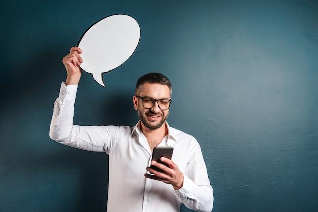 Vetri d'uso dell'uomo positivo che tengono fumetto che chiacchiera dal telefono.
