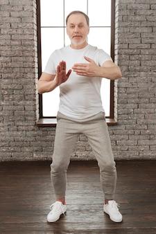 T-shirt bianca da portare dell'uomo positivo mantenendo le braccia piegate sui gomiti guardando dritto sulla fotocamera