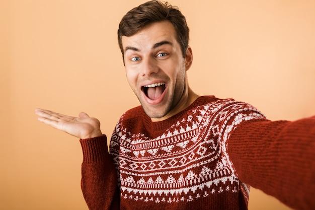 Uomo positivo con setole che indossa un maglione lavorato a maglia ridendo e tenendo il copyspace sul palmo mentre si scatta una foto selfie, isolata sul muro beige