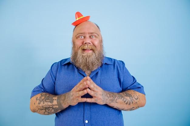 Uomo positivo con sovrappeso che indossa un piccolo sombrero e una camicia blu su sfondo azzurro