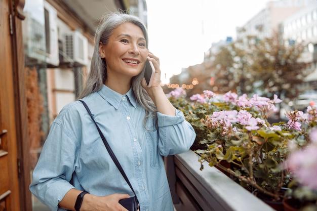 La signora asiatica matura positiva in camicia blu parla al telefono cellulare sul terrazzo con i fiori