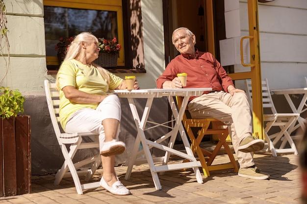 L'uomo e la donna maturi positivi con bevande riposano al tavolino nell'accogliente street cafe