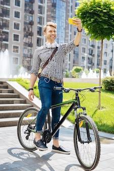 Ricordi positivi. piacevole uomo felice che sorride mentre scatta foto di se stesso sulla bicicletta