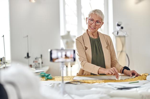 Una donna di mezza età positiva disegna un motivo sul video di ripresa del tessuto per il blog in officina
