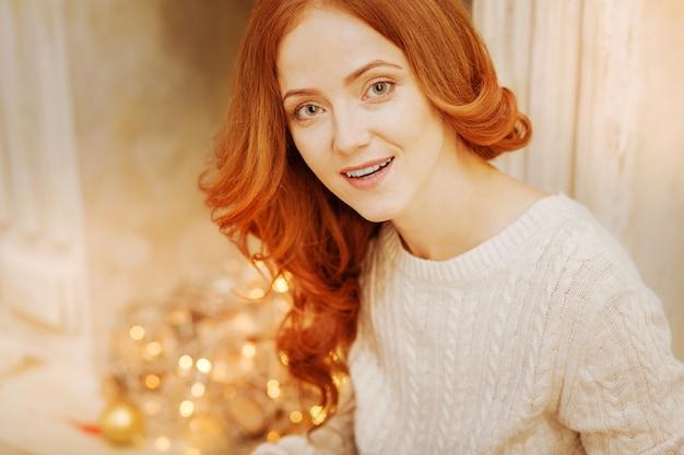 Pensiero positivo. donna graziosa della testarossa che indossa un maglione lavorato a maglia caldo che sorride