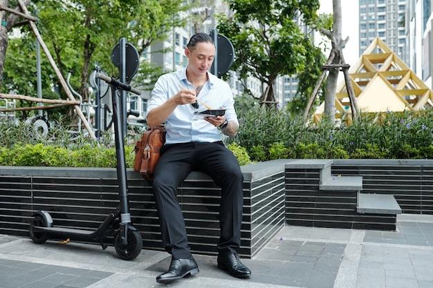 Imprenditore di razza mista positivo seduto sul parapetto e mangiando delizioso cibo di strada a pranzo