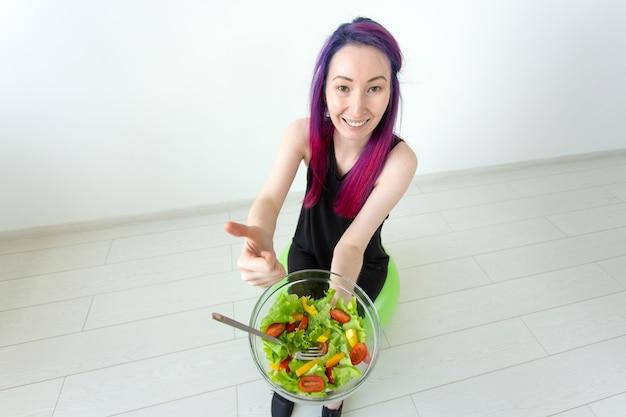 Ragazza hipster di razza mista positiva con capelli colorati che mangia un'insalata greca leggera dopo l'allenamento fisico su una priorità bassa bianca. il concetto di corretta alimentazione e perdita di peso. spazio pubblicitario
